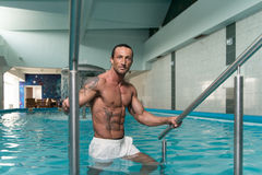 Manlig simmare Resting In Pool arkivbild
