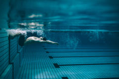Manlig simmare som över vänder i simbassäng Royaltyfri Bild