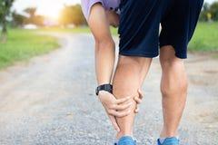 Manlig skada för för idrottsman nenlöparemuskel och ankel, når att ha joggat Athle royaltyfri bild