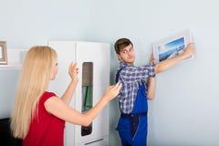 Manlig snickare Hanging Picture Frame på väggen fotografering för bildbyråer