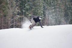 Manlig snowboarder som hoppar över lutningen i vinterdag Royaltyfria Foton