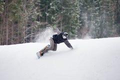 Manlig snowboarder som hoppar över lutningen i vinterdag Arkivfoto