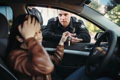 Manlig snut i kvinnlig chaufför för enhetlig kontroll på vägen royaltyfria foton