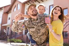 Manlig soldat som återförenas med hans familj, utomhus Militärtjänst royaltyfria foton