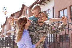 Manlig soldat som utomhus återförenas med hans familj Militärtjänst royaltyfri bild
