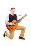 Manlig som leker en gitarr och sjunga Arkivfoton