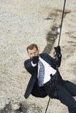 Manlig spion som siktar handeldvapnet, medan Rappelling Fotografering för Bildbyråer
