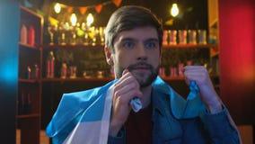 Manlig sportfan med den h?llande ?gonen p? matchen f?r Argentina flagga i bar, rubbning om nederlag lager videofilmer