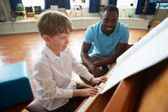 Manlig student Enjoying Piano Lesson med läraren royaltyfria bilder