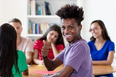 Manlig student för lyckad afrikansk amerikan som lär med gruppen av studenter arkivfoto