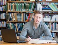 Manlig student med bärbara datorn som studerar i universitetarkivet fotografering för bildbyråer