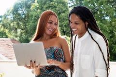 Manlig student med dreadlocks och flickvän som ser bärbara datorn fotografering för bildbyråer