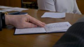 Manlig student med en lärare i klassrum Läraren skriver bedömningen i gradebooken royaltyfri fotografi