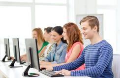 Manlig student med klasskompisar i datorgrupp arkivbild