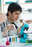 Manlig student som arbetar med mikroskopet royaltyfria bilder
