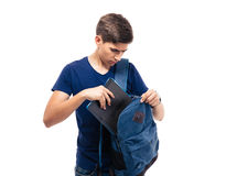Manlig student som sätter mappen i ryggsäck royaltyfri fotografi