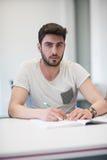 Manlig student som tar anmärkningar i klassrum fotografering för bildbyråer