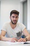 Manlig student som tar anmärkningar i klassrum arkivbild