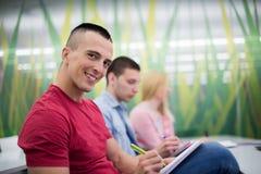 Manlig student som tar anmärkningar i klassrum royaltyfri bild