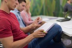 Manlig student som tar anmärkningar i klassrum arkivfoto