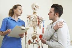 Manlig tålmodig beskriva skada till osteopaten royaltyfria bilder