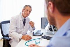 Manlig tålmodig ha konsultation med doktor In Office Arkivfoto