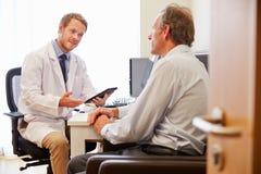 Manlig tålmodig ha konsultation med doktor In Office Royaltyfria Bilder