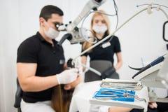 Manlig tandläkare- och kvinnligassistent som behandlar tålmodiga tänder med mikroskopet på det tand- klinikkontoret tand- utrustn arkivfoton