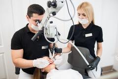 Manlig tandläkare- och kvinnligassistent som behandlar tålmodiga tänder med tand- hjälpmedel på det tand- klinikkontoret arkivfoton