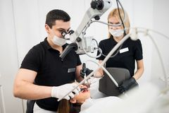 Manlig tandläkare- och kvinnligassistent som kontrollerar upp tålmodiga tänder med tand- hjälpmedel tand- utrustning royaltyfri bild