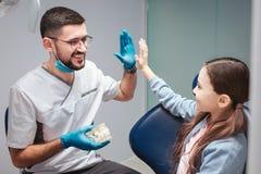 Manlig tandläkare som ger högt fem till flickan i tand- stol De är i rum Konstgjord käke för grabbhåll med tänder Lyckligt och arkivfoto