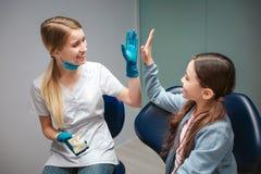 Manlig tandläkare som ger högt fem till flickan i tand- stol De är i rum Konstgjord käke för grabbhåll med tänder Lyckligt och royaltyfri fotografi