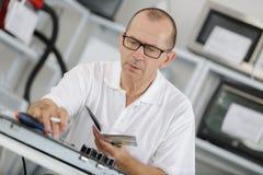 Manlig tekniker som läser handboken på arbetsplatsen Arkivbilder