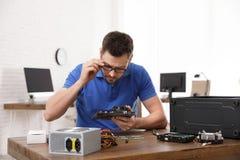 Manlig tekniker som reparerar datoren p? tabellen fotografering för bildbyråer