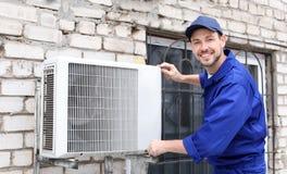 Manlig tekniker som reparerar luftkonditioneringsapparaten Arkivbild