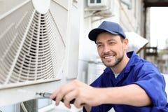 Manlig tekniker som reparerar luftkonditioneringsapparaten Arkivfoton