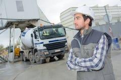 Manlig tekniker som står den främsta lastbilen på byggnadsplats Arkivfoton