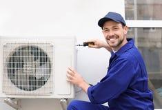 Manlig tekniker som utomhus reparerar luft Fotografering för Bildbyråer