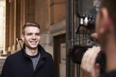 Manlig televisionpresentatör Filming Outdoor Report Royaltyfri Foto