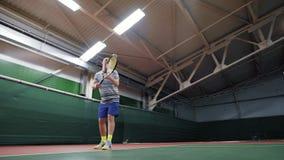 Manlig tennisspelare som tjänar som bollen Sportfritid och övning Inomhus domstol stock video