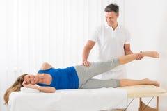 Manlig terapeut Giving Leg Massage till kvinnan royaltyfri foto