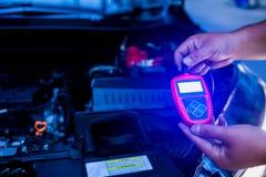 Manlig tester för mekanikerinnehavbatteri, når att ha ändrat bilbatteriet arkivfoton