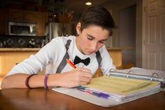 Manlig tonårig görande läxa i kök Royaltyfri Fotografi