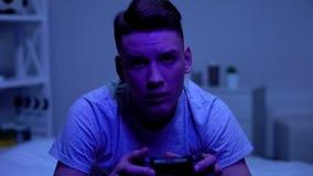 Manlig tonåring med styrspaken som spelar videospelet på natten som spelar böjelse arkivfoto
