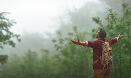 Manlig turist överst av berget i dimma i höst Arkivbild
