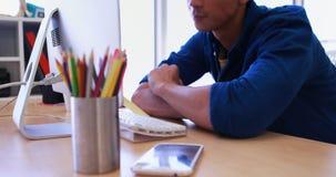 Manlig utövande användande persondator på hans skrivbord 4k stock video