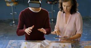 Manlig utövande användande virtuell verklighethörlurar med mikrofon på skrivbordet 4k lager videofilmer