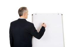 Manlig utövande handstil på en flipchart Arkivbild