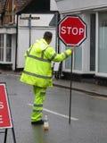 Manlig vägarbetare med det gula fluorescerande omslaget och byxa som rymmer det röda tecknet för stopp royaltyfria bilder