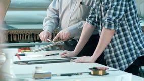 Manliga arbetare som mäter format av ramen bak skrivbordet i seminarium Arkivbild